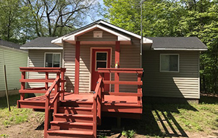 Cabin with siding, front deck and stairs