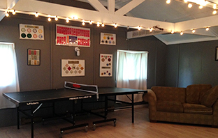 Inside a cabin with a pingpong table and couch