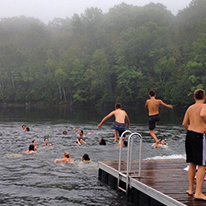Kids jumping off dock into lake