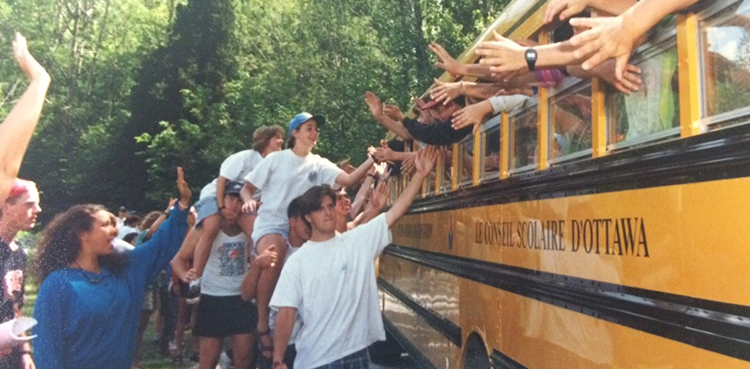 Camp Members high fiving other camp members on school bus