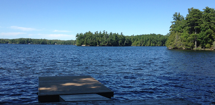 Dock on the lake with forested islands in the distance